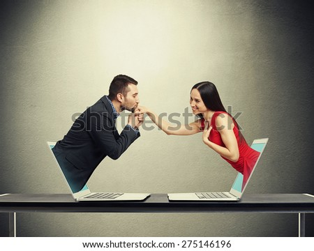 concept of love in social network. young man got out of the computer and kissing hand of beautiful young woman who got out of another computer over dark grey background - stock photo
