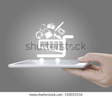 Concept of mobile online shopping. Hand holding tablet or large smart phone in front of grey background. Shopping cart icon with reflections on smart phone.
