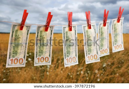 Concept of money laundering - dollars are drying on cord on field background - stock photo