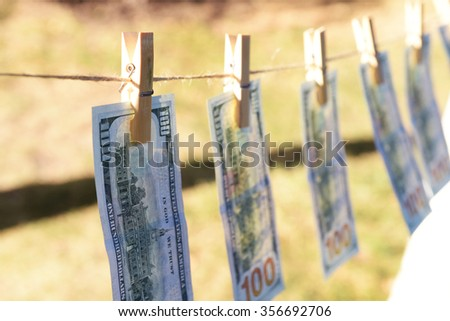 Concept of money laundering - one hundred bills hanging on a cord, outdoors - stock photo