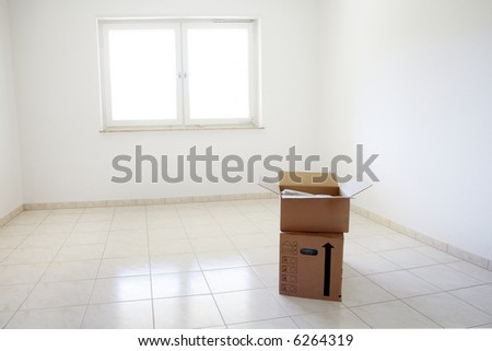 Concept of moving - empty room with moving boxes - stock photo