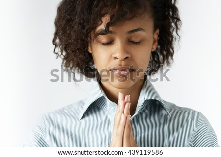 Concept of praying and consideration. Headshot of strong featured African woman with shaggy hair, closed eyes, clasping her hands in meditation and prayer, thinking about peace, gratitude and Universe - stock photo
