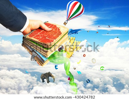 Concept of reading. Man's hand holding magic book with falling letters, animals and other objects from this book. Concept of dreaming. - stock photo