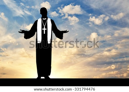 Concept of religion. Priest praying silhouette against the evening sky in the sun - stock photo