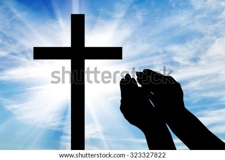 Concept of religion. Silhouette of hands outstretched on the cross against a beautiful sky