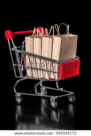concept of sale shopping cart with paper bags is isolated on black background, closeup - stock photo