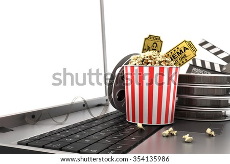 Concept of see online film. Film reels, clapperboard and pop corn on laptop keyboard. - stock photo