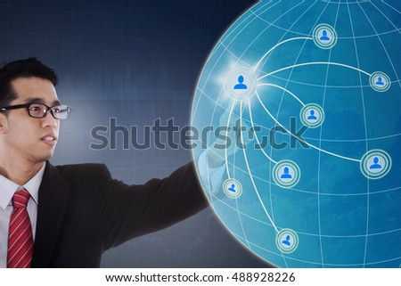 Concept of social network with a young businessman touching virtual icon of social network with globe on the futuristic screen