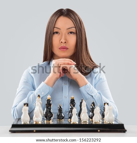 Concept of Strategy in business - business woman sitting in front of chess and planning  - stock photo
