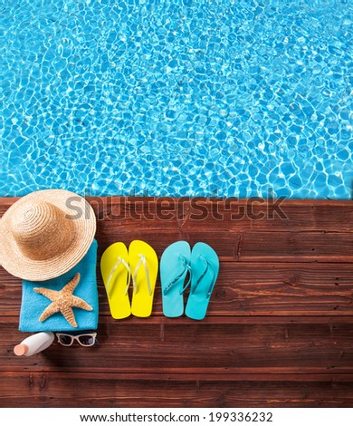 Concept of summer accessories on wood with blue water
