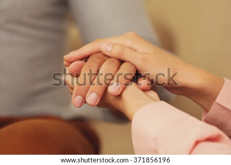 Concept of support - man and woman holding hands in the room