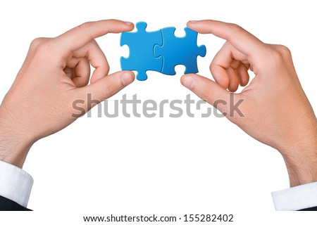 Concept of teamwork - hands connect two puzzle pieces - stock photo