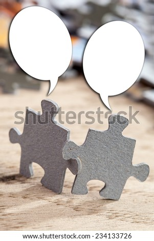 Concept of teamwork: Two jigsaw puzzle pieces on a table joint together with talking bubbles. Shallow depth of field - stock photo