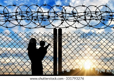 Concept of the family of refugees. Silhouette of mother and child refugees near the border fence in the distance against the backdrop of the city at sunset - stock photo
