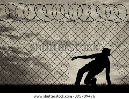 Concept of the refugees. Silhouette of refugees crossed the border illegally through the hole in the fence - stock photo