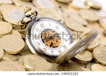 Concept of time is money, old watch on a pile of coins - stock photo