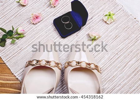 Concept of wedding fashion, beauty and wedding ceremony. Beige patent leather shoes with gold buckle, two wedding rings of white gold and sprig of delicate pink roses on the table.   - stock photo