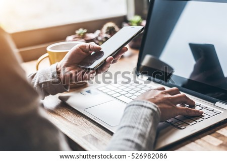 concept of working at home with laptop on table and using cellphone