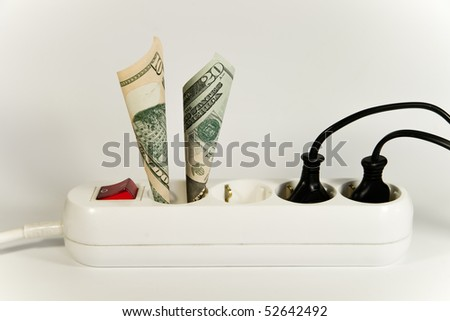Concept on rising energy price. Shown is a household power socket with a switch and some plugs and wires and some US Dollar banknotes.