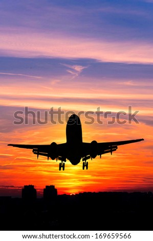 Concept or conceptual black plane, airplane or aircraft silhouette flying over sky at sunset or sunrise background - stock photo