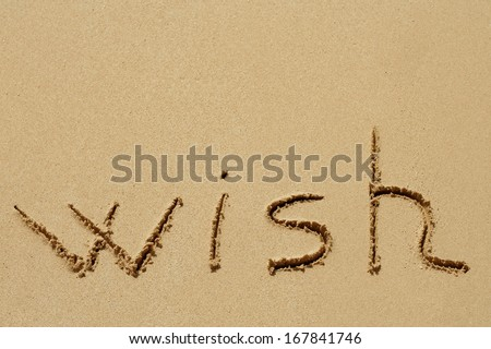 Concept or conceptual hand made or handwritten wish text in sand on a beach in an exotic island - stock photo
