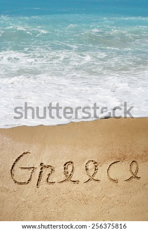 Concept or conceptual hand or handwritten Greece  text in sand on beach in exotic island, metaphor to summer, ocean, sea, travel, vacation, tourism, tropical, coast, resort, paradise, sunny or water - stock photo