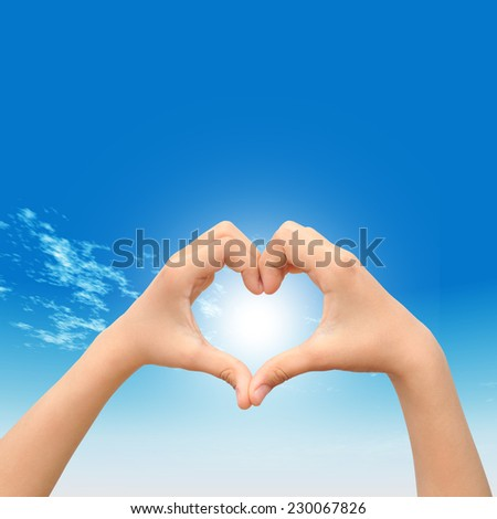 Concept or conceptual heart shape or symbol made of human or woman and man hand over a blue sky background, metaphor to love, valentine, romantic, couple, wedding, romance, summer or sunrise - stock photo