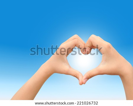 Concept or conceptual heart shape or symbol made of human or woman and man hand over a blue sky at sunset background, metaphor to love, valentine, romantic, couple, wedding, romance, summer or sunrise - stock photo