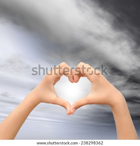 Concept or conceptual human male or man and woman hands in love, Valentines shape or symbol of heart over blue sky background - stock photo