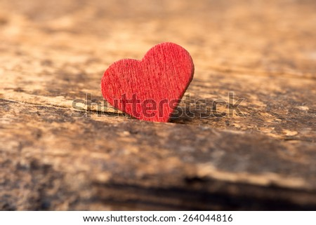 Concept photo for love showing a red wood heart on a rustic wood plank - stock photo