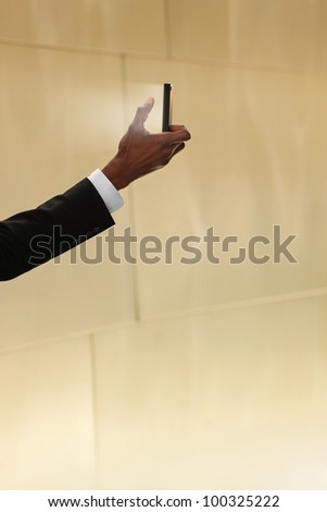 Concept photo of a man holding a glowing cell phone against neutral warm background with lots of copy space - stock photo