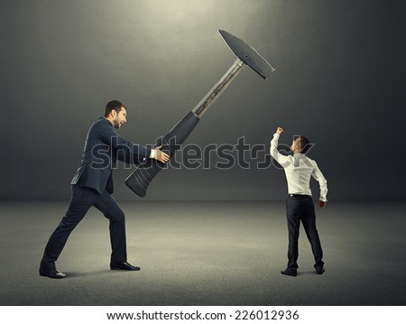 concept photo of conflict between businessmen. small businessman showing fist and looking at big hammer. photo in the dark room - stock photo