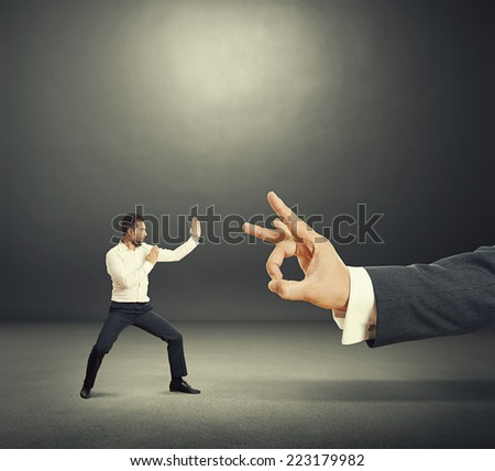 concept photo of conflict between subordinate and boss. angry young businessman ready for fight with big flick of his boss. photo in the dark room - stock photo