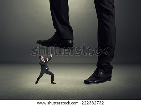 concept photo of conflict between subordinate and boss. angry young businessman showing fist and looking up at big boss. photo in the dark room - stock photo
