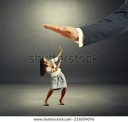 concept photo of conflict between subordinate and boss. scared businesswoman looking up at big palm of his boss and screaming in the dark room - stock photo