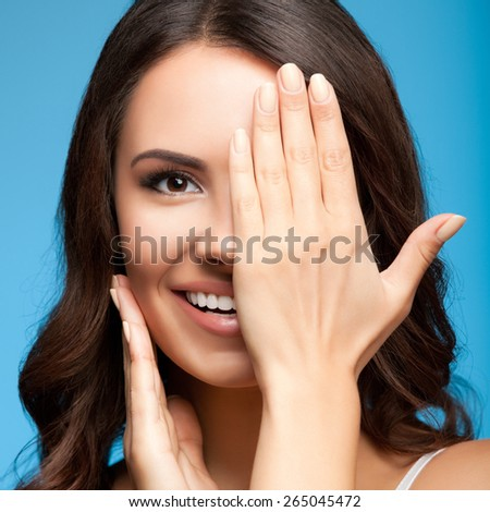 Concept photo of happy smiling young woman with one eye, closed by hand, covering part of her face, over blue background - stock photo