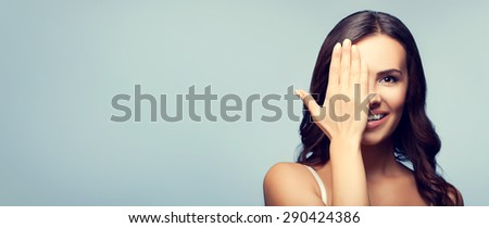 Concept photo of happy smiling young woman with one eye, closed by hand, covering part of her face, with blank copyspace area for text or slogan - stock photo