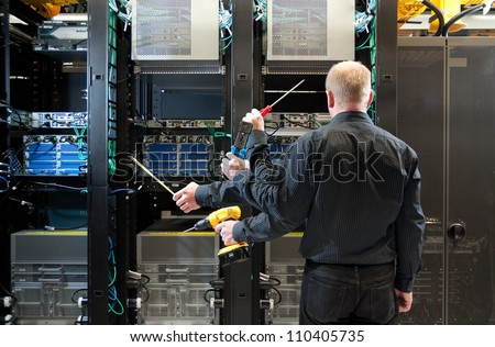 Concept photo of Network administrator installing equipment. Multiple tools shown with multiple hand positions.