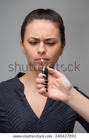 Concept photo of woman smoking cigarette and a hand with lighter, quit smoking addiction concept, isolated on grey - stock photo