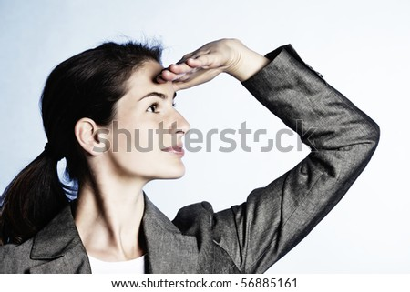 Concept: Positive business outlook. Young businesswoman looking far ahead, on light-blue background. - stock photo