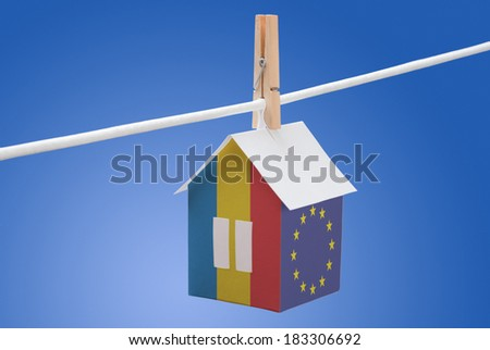 concept - Romania, Romanian and EU flag painted on a paper house hanging on a rope - stock photo