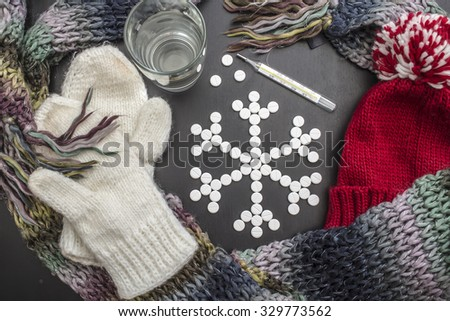 concept snowflakes made from medicinal tablets, lie close colorful winter clothes, a glass of water and a thermometer. - stock photo