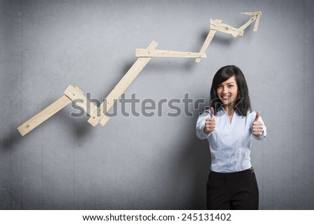 Concept: Succeeding in career or business. Young happy businesswoman holding thumbs up in front of positive trend graph,  isolated on grey background. - stock photo