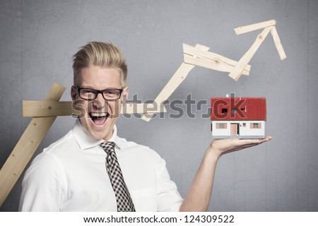 Concept: Success in real estate market. Happy businessman holding model house in hand in front of ascending business graph, isolated on grey background. - stock photo