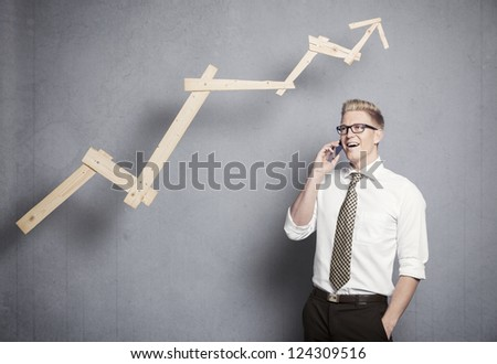 Concept: Successful business. Confident young businessman on the mobile-phone in front of rising business graph, isolated on grey background. - stock photo