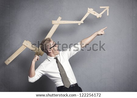 Concept: Successful business trend. Happy talented businessman pointing arm upwards in front of ascending business graph, isolated on grey background. - stock photo