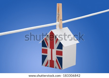concept - UK, british, britain flag painted on a paper house hanging on a rope - stock photo