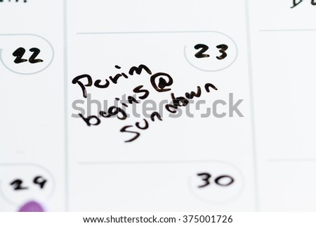 concept using a calendar on march 23 and the words Purim begins at sundown hand written on it - stock photo