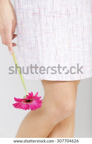Concept view of woman legs in purple dress holding a romantic flower by her side