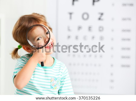 concept vision testing. child girl with a magnifying glass at the doctor ophthalmologist - stock photo
